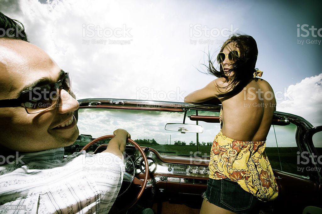 Young Man Driving Vintage Car with Woman Passenger royalty-free stock photo