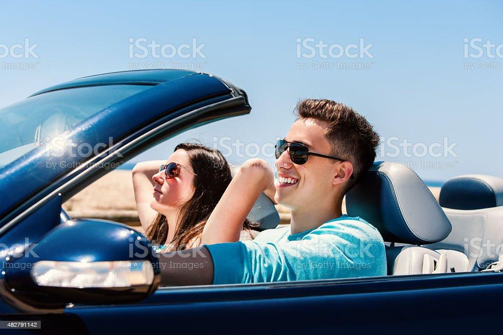 Jeune homme avec petite amie en voiture décapotable photo libre de droits
