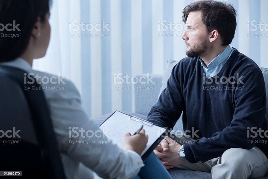 Young man during psychological therapy stock photo