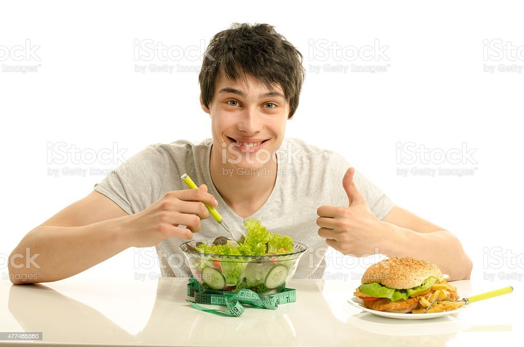Young man eating a healthy salad instead of.a big hamburger. stock photo