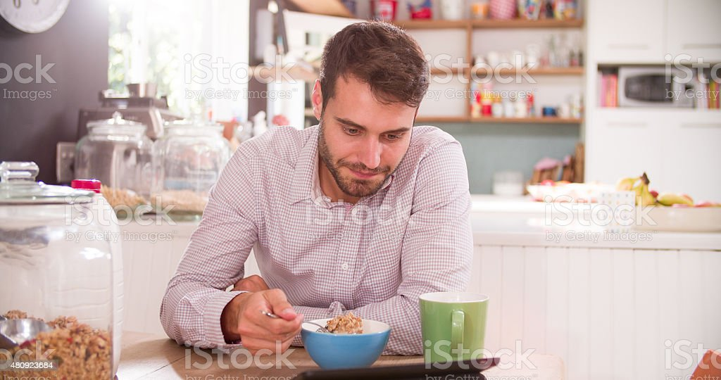 Young Man Eating Breakfast Whilst Using Digital Tablet stock photo