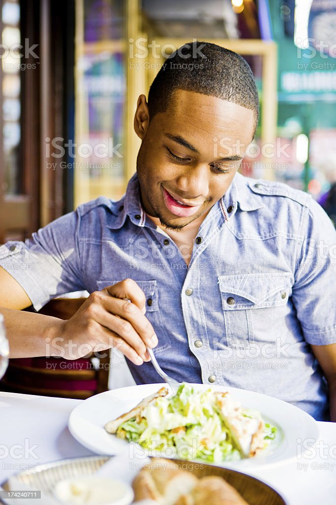 Young Man eating Ceasar Salad in a restaurant royalty-free stock photo