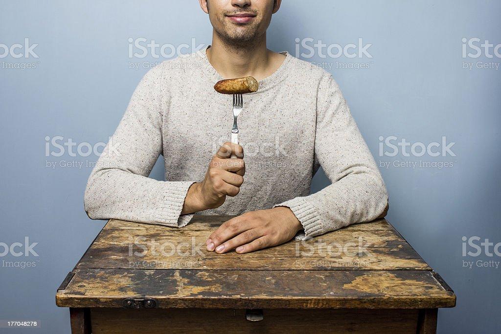 Young man eating sausage royalty-free stock photo