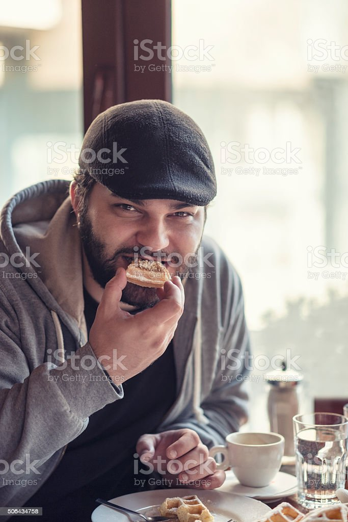 Young Man Eating Waffles for Breakfast at the Restaurant stock photo