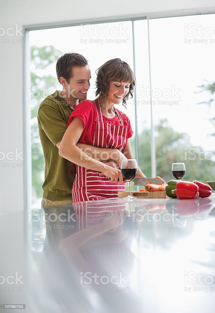 Young man embracing woman while she's preparing food in kitchen royalty-free stock photo