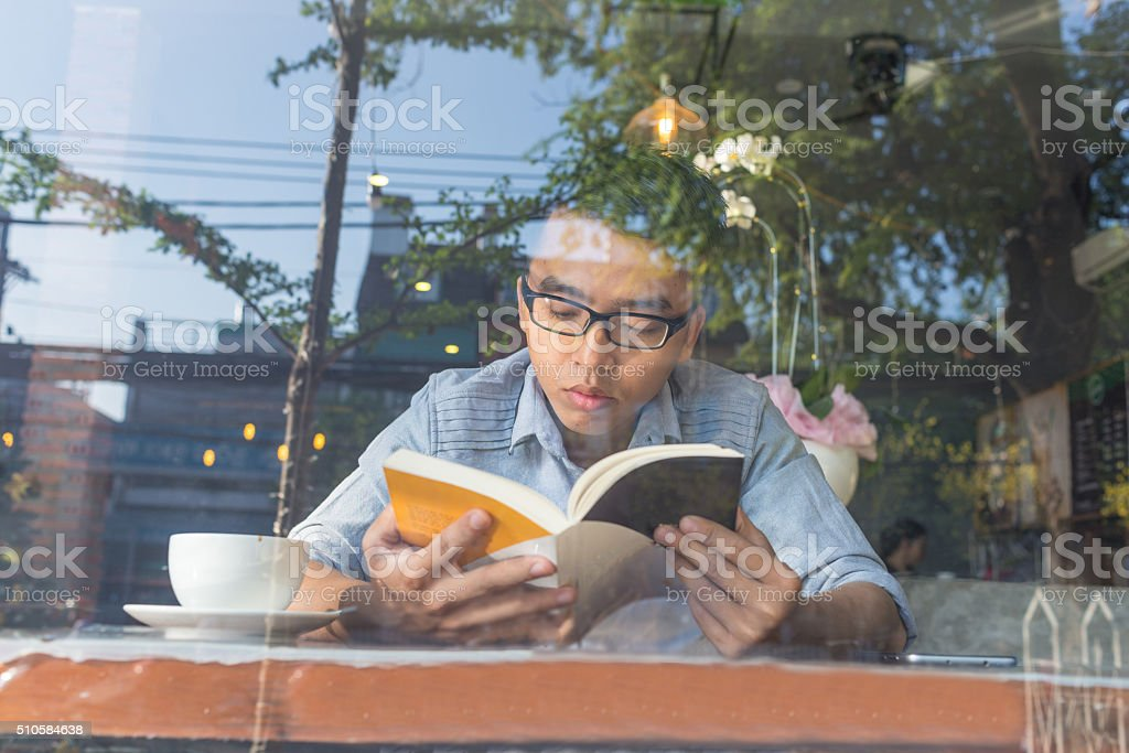 Young man enjoy free time with book and coffee stock photo
