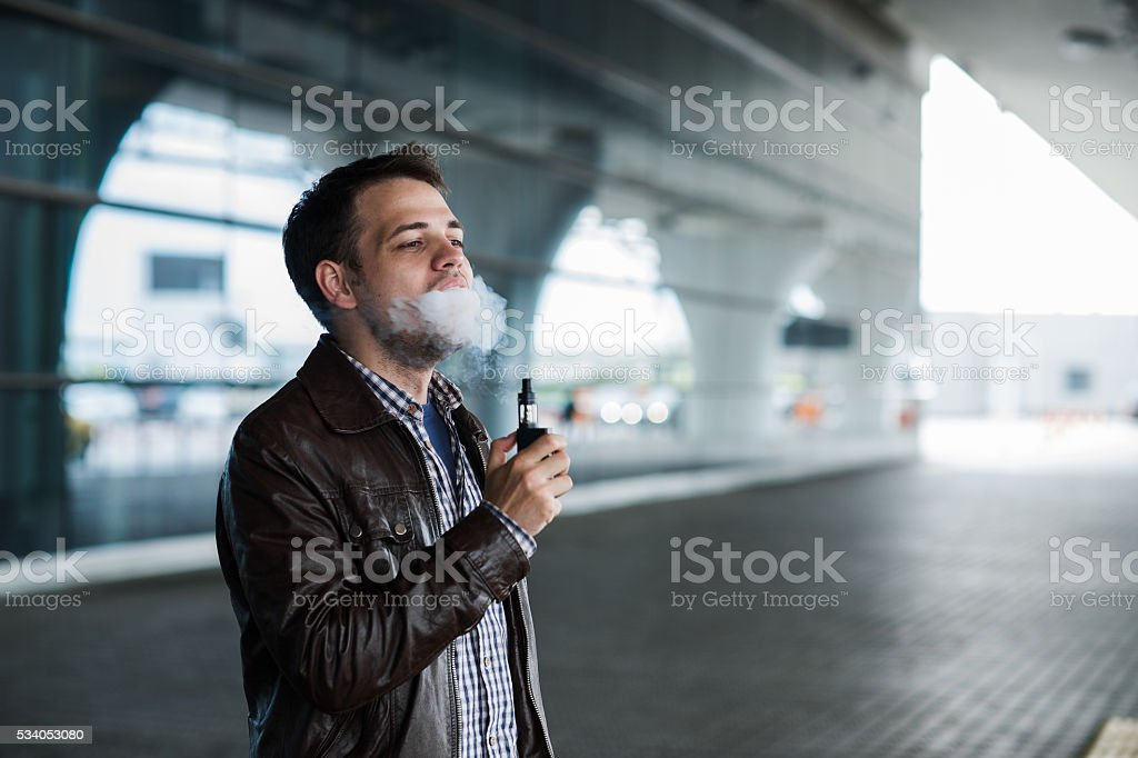 Young man enjoying a satisfying e-cigarette standing in profile stock photo