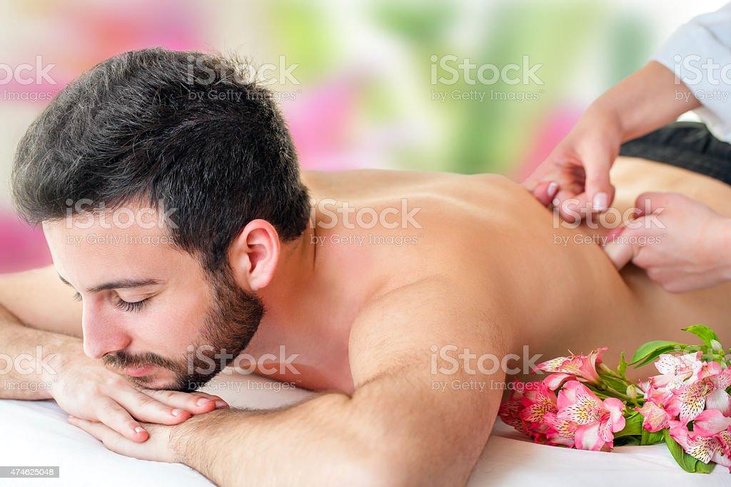 Jeune homme appréciant un massage du dos. photo libre de droits