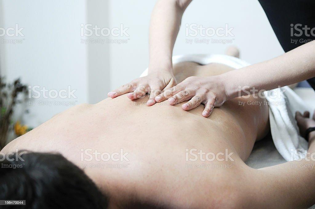Young man enjoying massage at spa stock photo