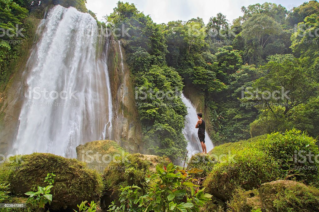 Young man enjoying nature at Cikaso Waterfall stock photo