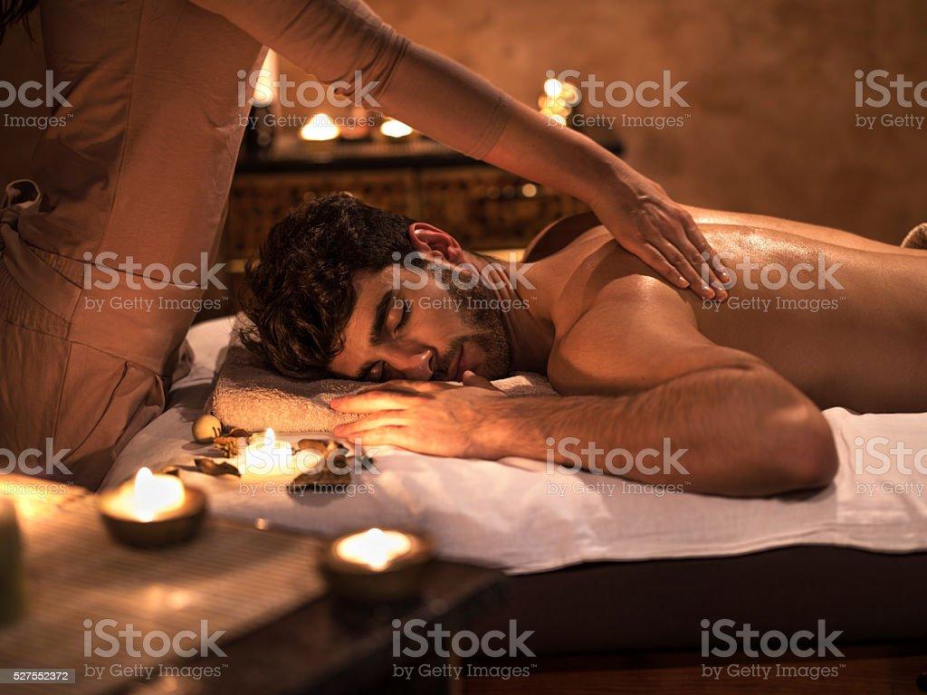 Young man enjoying with eyes closed during back massage. stock photo