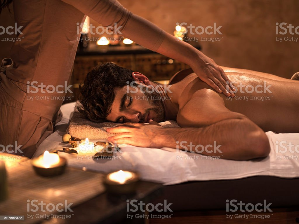 Young man enjoying with eyes closed during back massage. stock photo