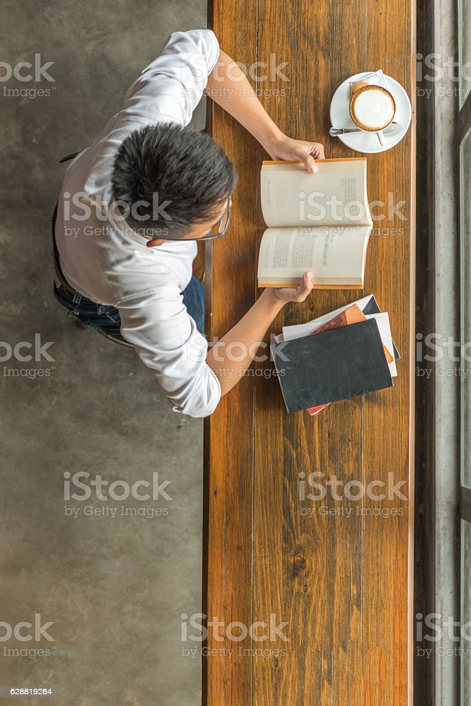Young man enjoys his day with books and hot cappuccino stock photo