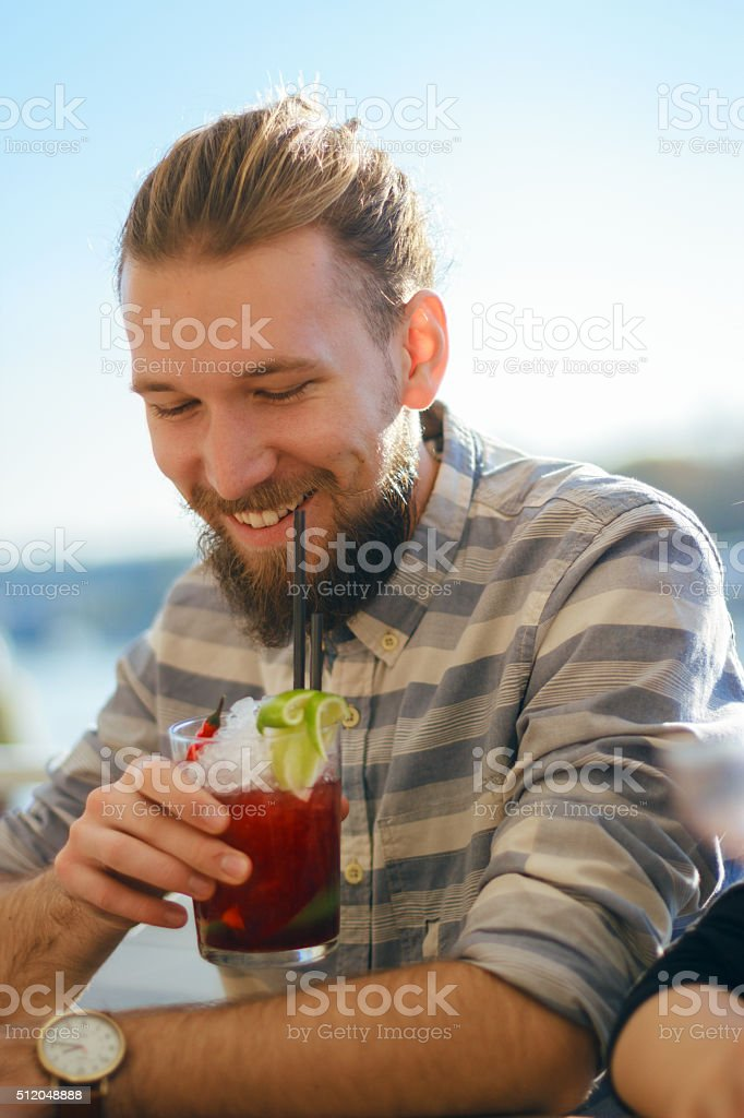 Young man enojying cocktail stock photo