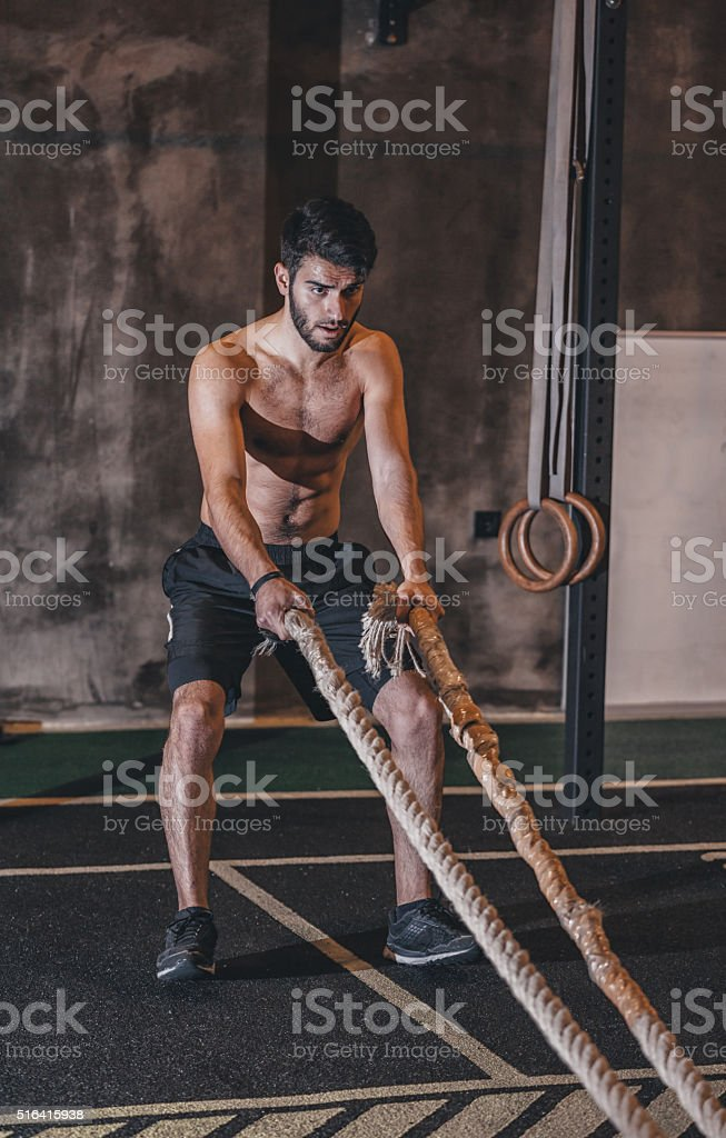 Young Man Excerising With Ropes stock photo