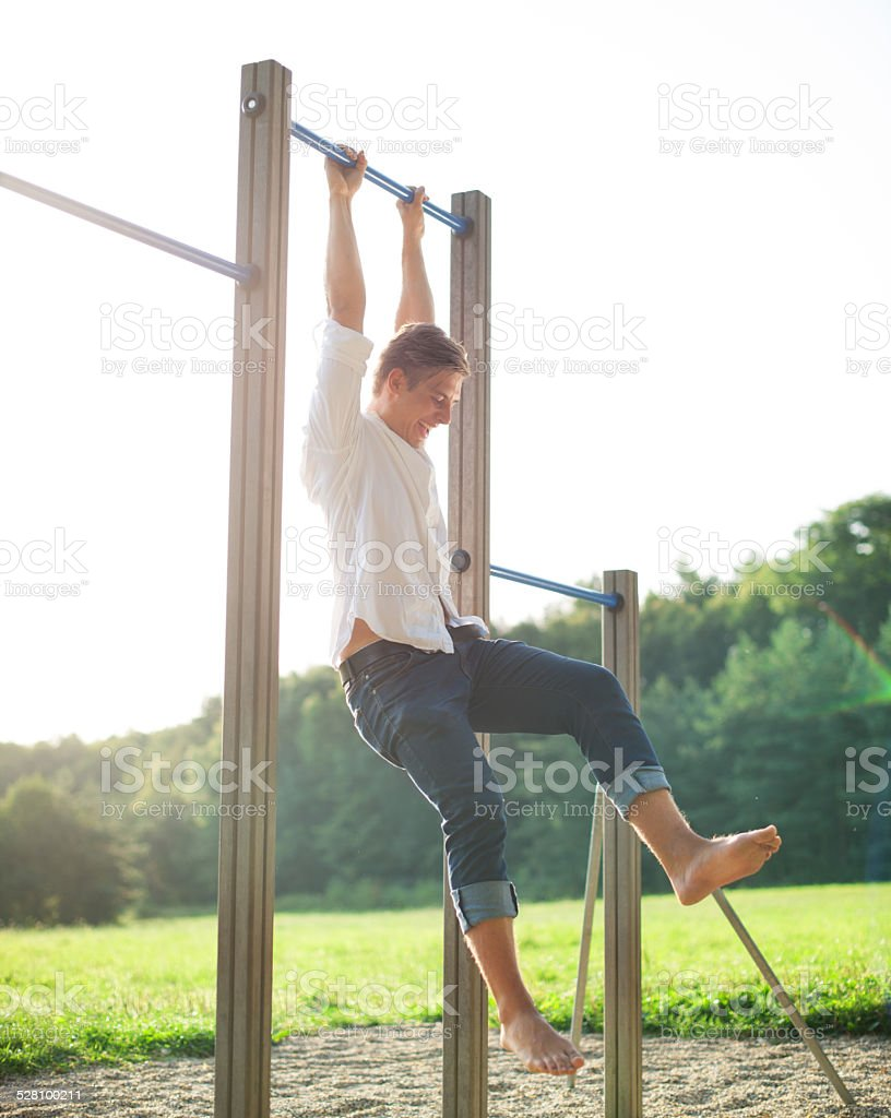 Young man exercising on bars at playground stock photo