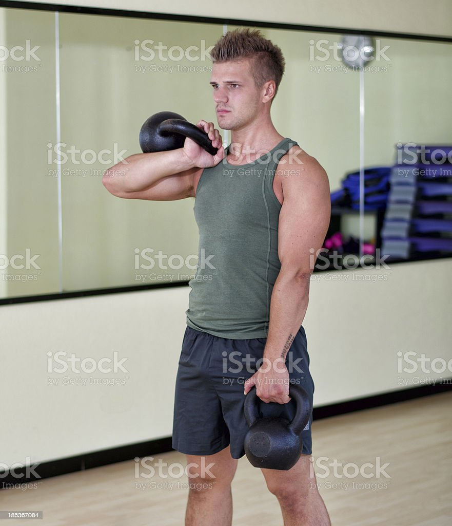 Young man exercising with kettlebells in gym royalty-free stock photo
