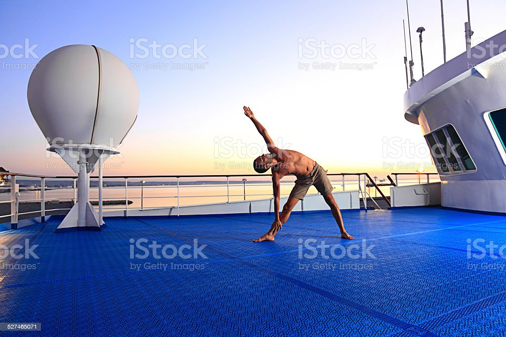 Young man exercising yoga on yacht deck stock photo