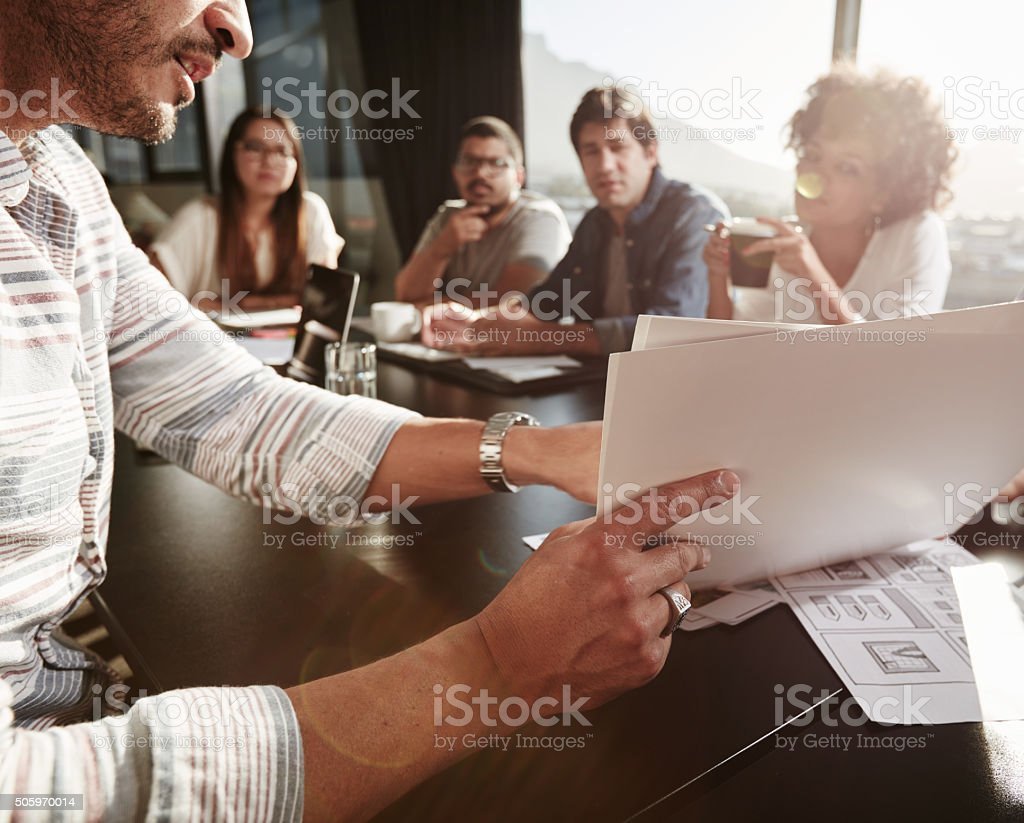 Young man explaining business plan to colleagues stock photo