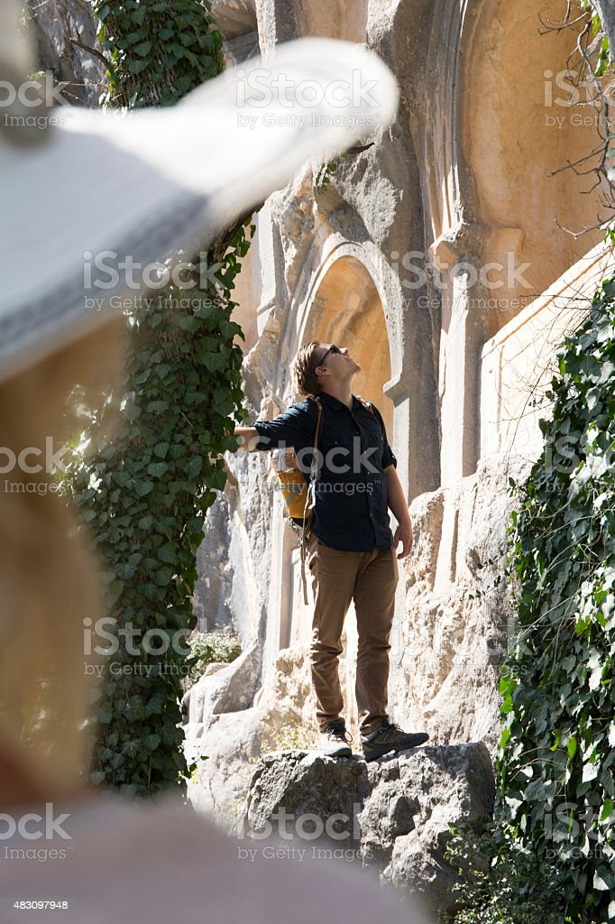 Young man explores necropolis, ancient Greek ruin stock photo