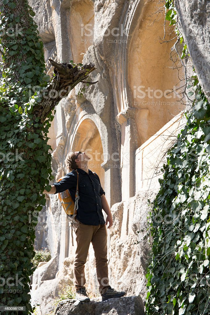 Young man explores necropolis, ancient Greek ruin stock photo