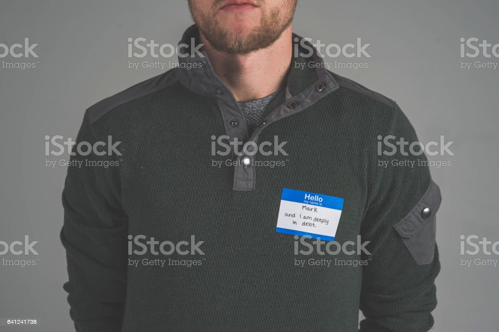 Young man facing audience with name tag that describes struggle 'debt' stock photo