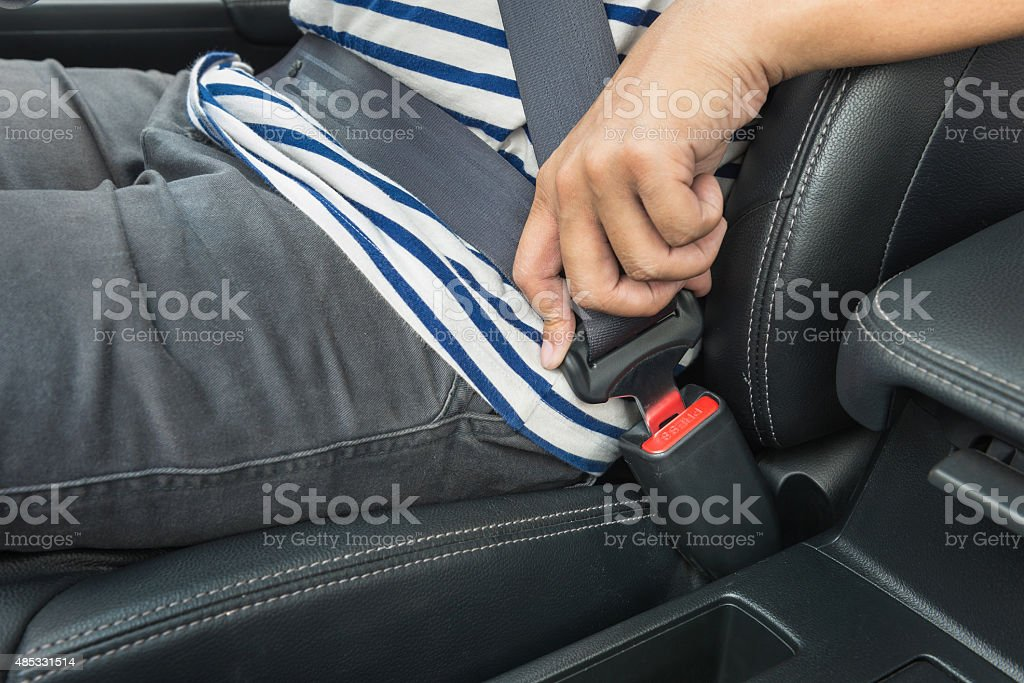 Young man fastening seat belt in the car stock photo
