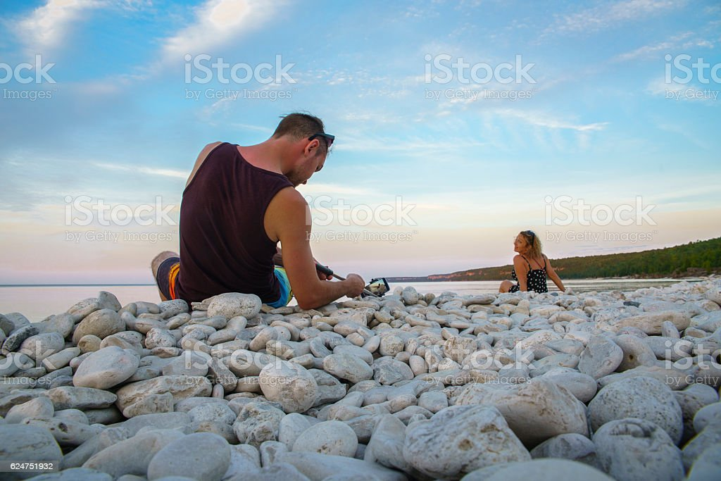 Young man filming the woman, Lake Huron, Tobermory, Ontario, Canada. stock photo