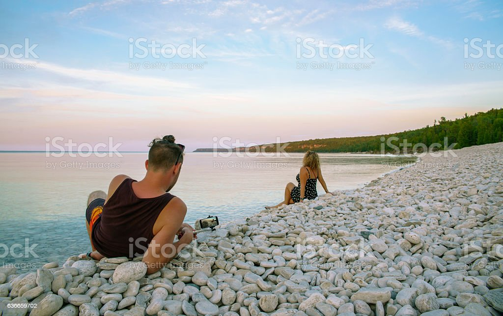 Young man filming the woman, Lake Huron, Tobermory, Ontario, Canada. stock photo