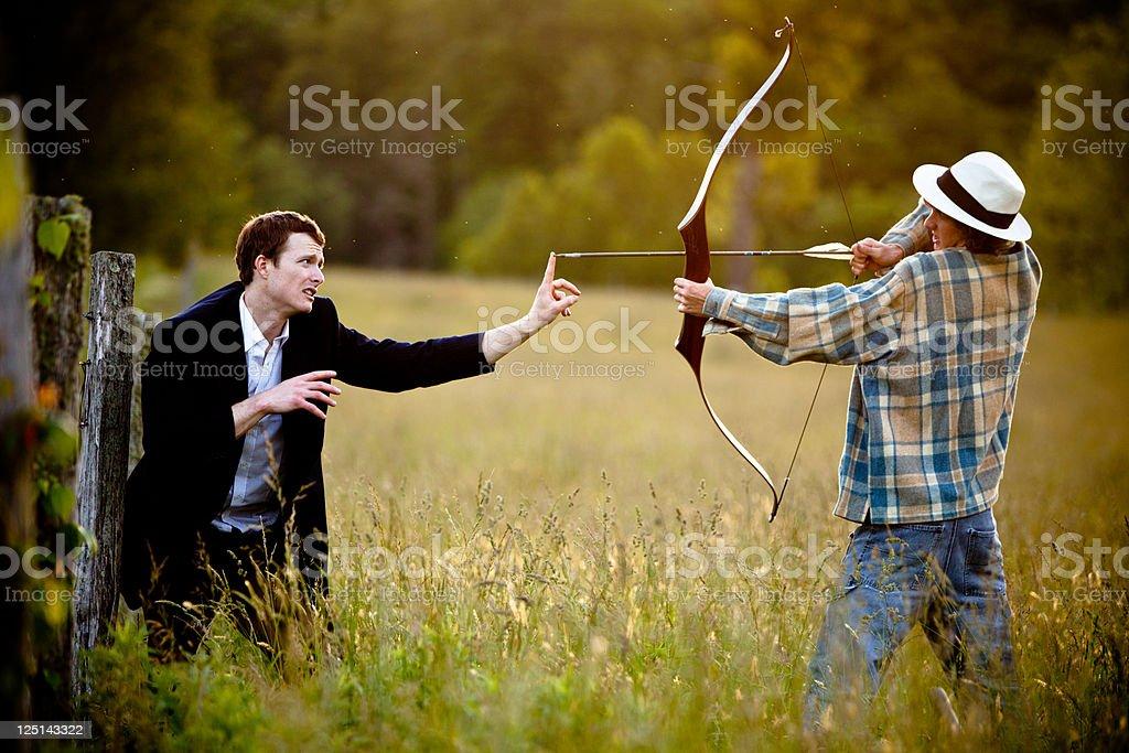 Young man firing bow and arrow towards a businessman stock photo