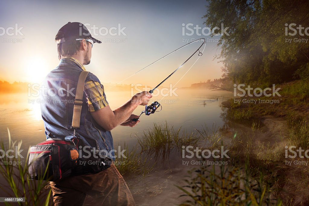 Young man fishing at misty sunrise stock photo