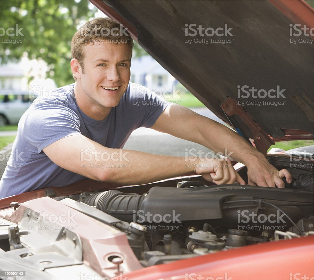 young man fixing engine of his car smiling stock photo