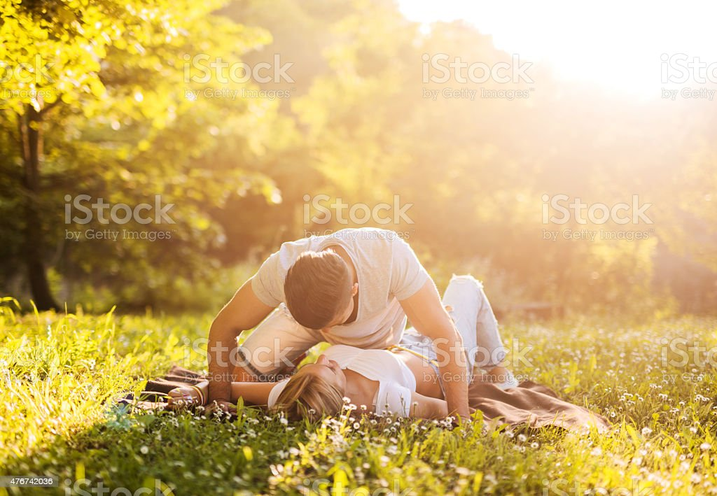 Young man flirting with his girlfriend at the park. stock photo