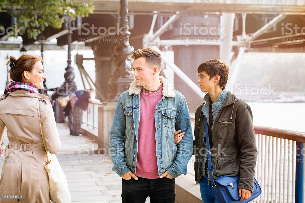Young man flirts passing female while out with girlfriend stock photo