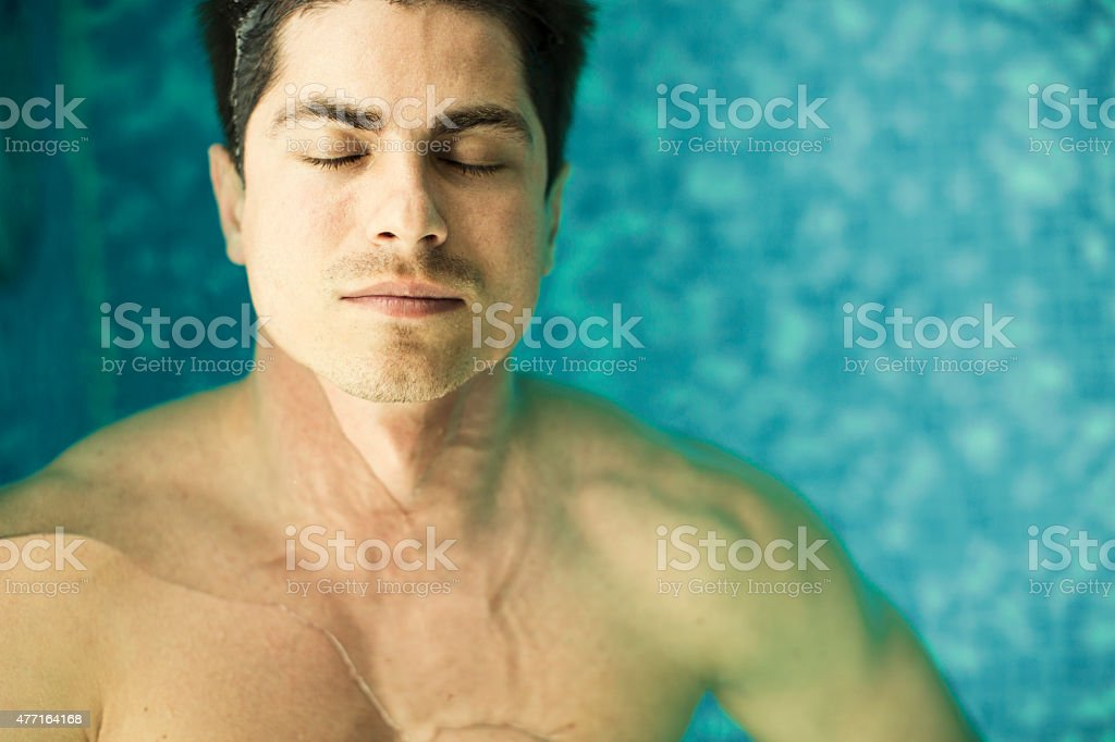 Young man floating in the swimming pool stock photo