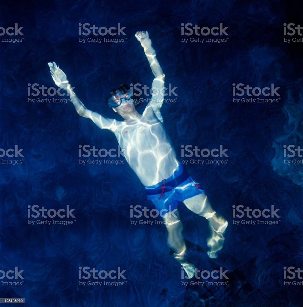 Young man floating underwater in ocean royalty-free stock photo