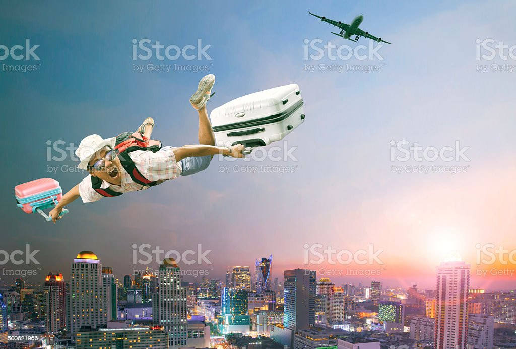 young man flying over urban scene stock photo