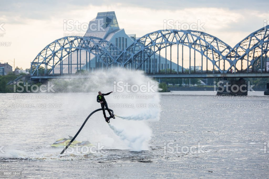 Young man flying through the air on a water flyboard stock photo