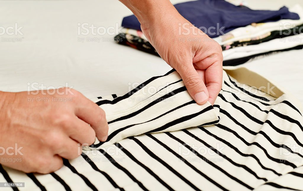 young man folding clothes stock photo