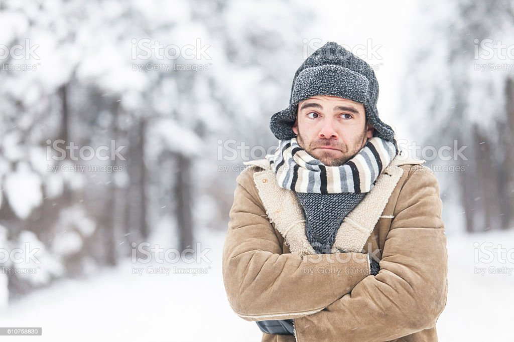 Young man freezing in the snow forest stock photo