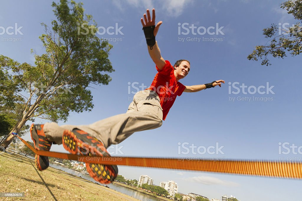 A young man from below doing slacklining tricks stock photo