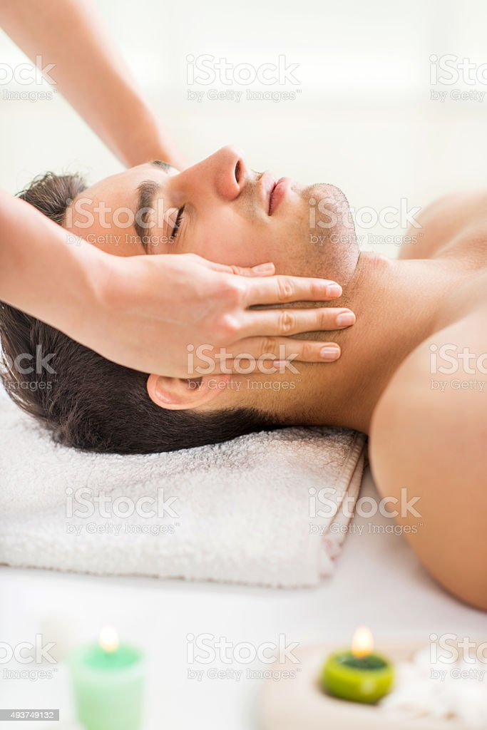 Young man getting facial massage at spa. stock photo