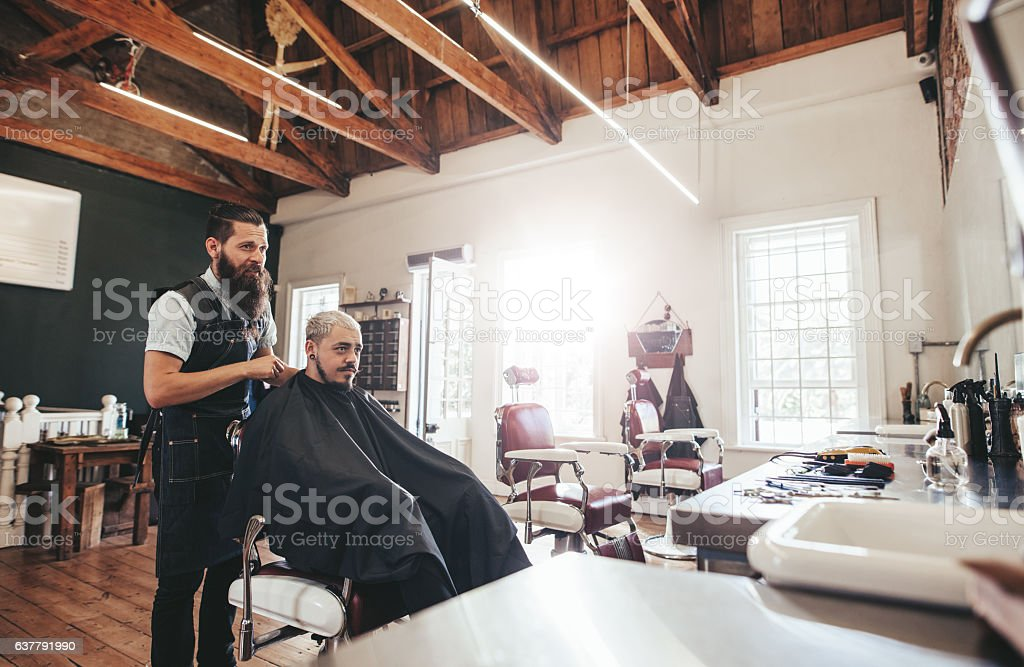 Young man getting haircut at barber shop stock photo