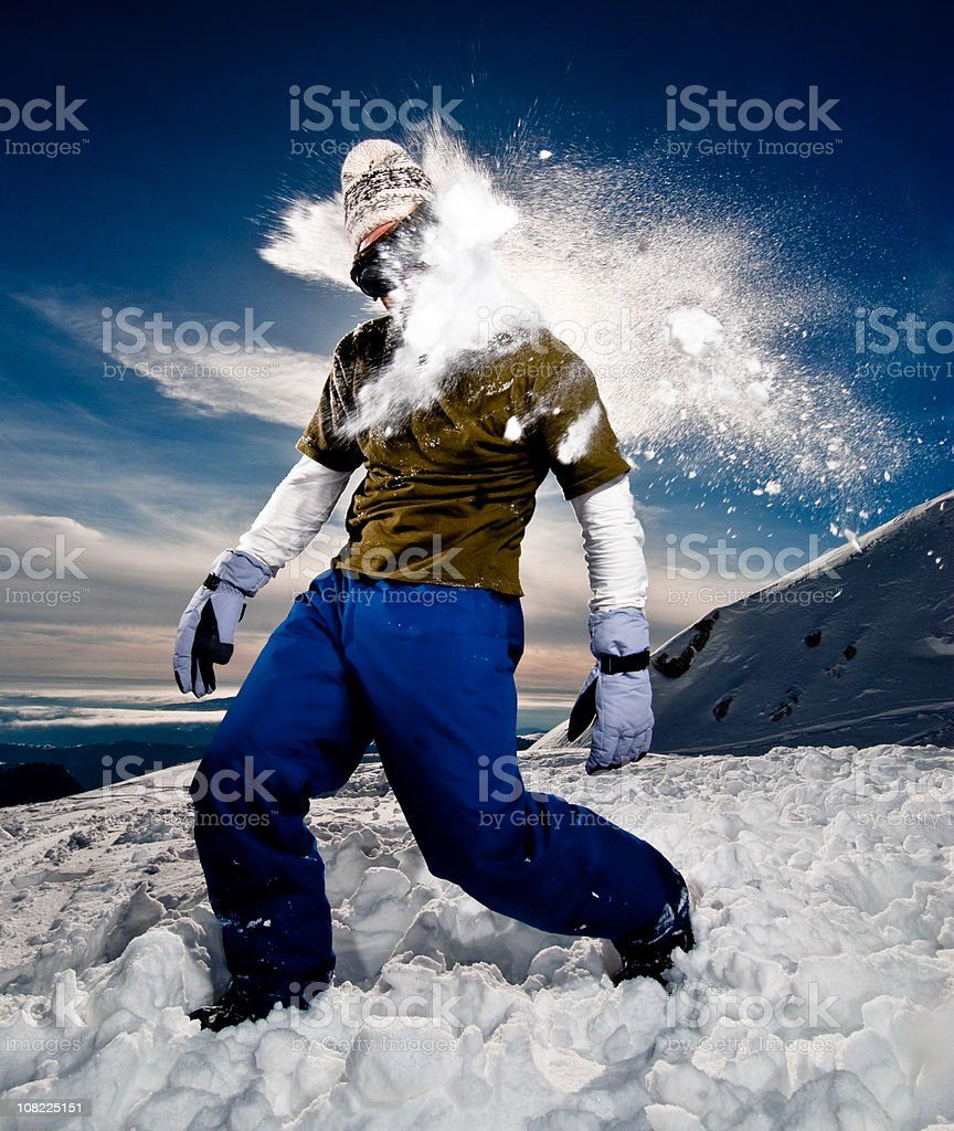 Young Man Getting Hit with Snowball on Mountains stock photo
