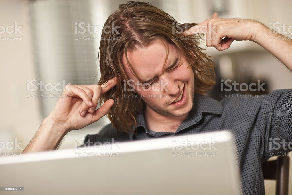 Young Man Getting Loopy While Using Laptop Computer stock photo