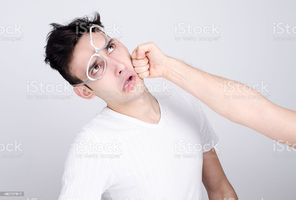 Young man getting punched in the jaw. stock photo