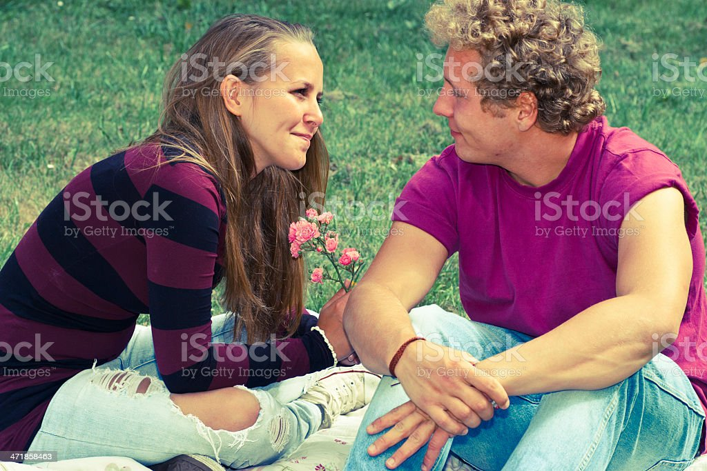 Young man gives a flower to his girlfriend royalty-free stock photo