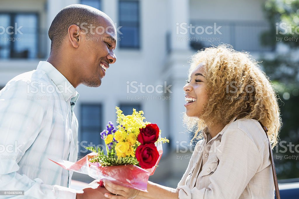 Young man gives flowers to girlfriend stock photo