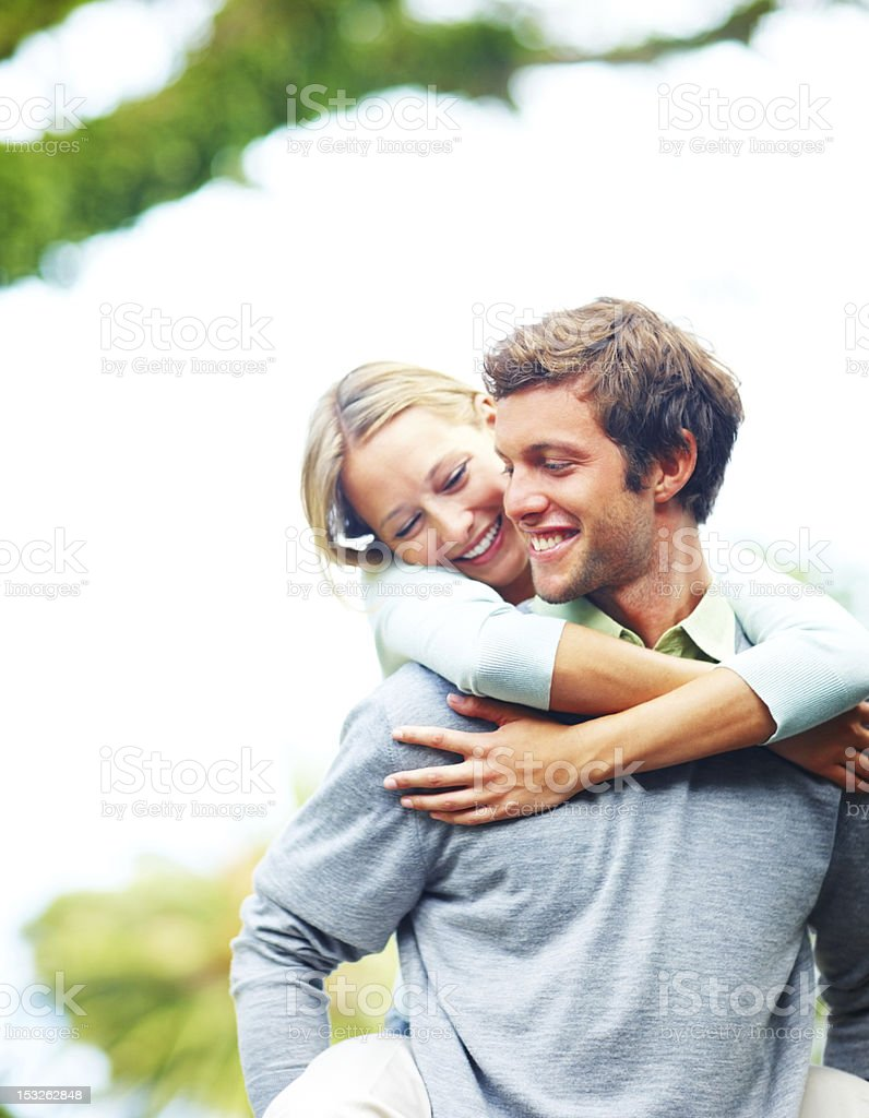 Young man giving piggyback to his girlfriend royalty-free stock photo