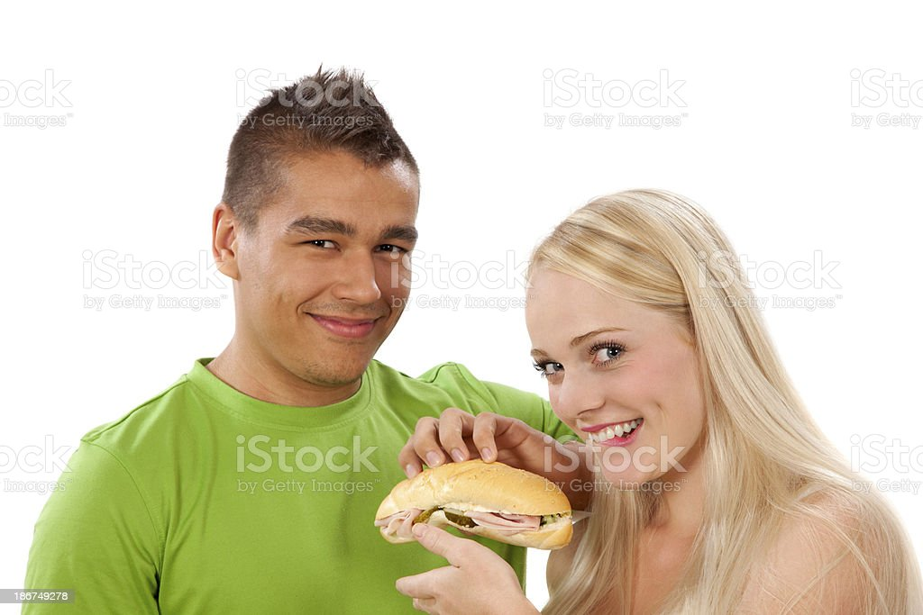 Young man giving sandwich to attractive woman royalty-free stock photo